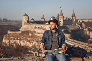 Traveler man with a map in his hands sits on background of old castle photo