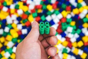Mano con ladrillos de plástico de colores sobre un fondo de colores foto