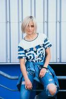 woman with short white hair stands on the background of metal wall photo
