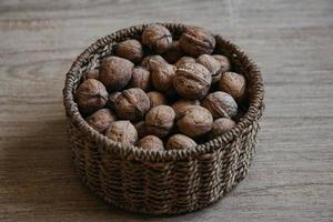 Walnuts in a round wicker basket on a wooden background photo