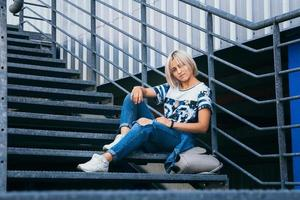 woman with short white hair in urban style sits on the metal stairs photo