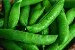 crop of peas lies in a round wicker basket on a wooden background photo