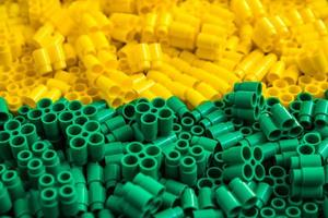 Plastic bricks of yellow and green. Details of toys. Close up. photo