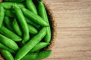 The crop of peas lies in a round wicker basket on a wooden background photo