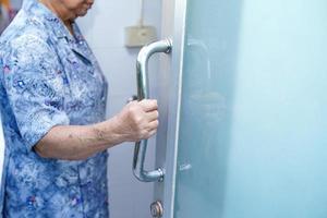 Mujer mayor asiática paciente uso inodoro baño manejar seguridad foto