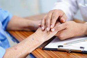 Doctor sosteniendo tocar las manos paciente mujer senior asiática con amor foto