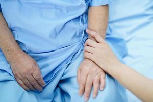 Tocar las manos paciente mujer senior asiática con amor foto