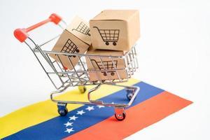 caja con logo de carrito de compras y bandera de venezuela, importación y exportación foto