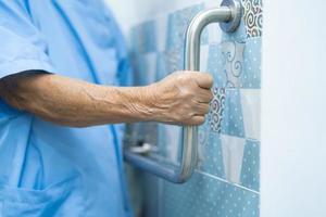 Asian senior woman patient use toilet bathroom handle security photo