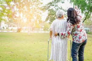 Ayude y cuide a la mujer mayor asiática use el andador en el parque. foto