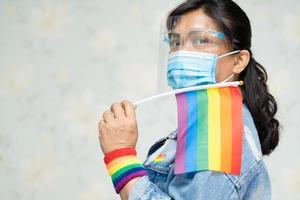 dama asiática sosteniendo la bandera de colores del arco iris, símbolo de lgbt foto