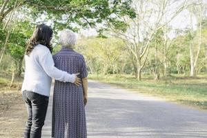 Ayudar y cuidar a la mujer mayor asiática a caminar en el parque. foto