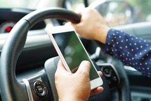 Holding mobile phone in car to communication photo