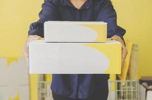 una mano humana que sostiene el paquete y el buzón para la entrega y el envío. foto