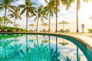 Beautiful luxury umbrella and chair around outdoor swimming pool photo