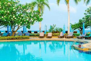 Chair, pool, and umbrella around swimming pool with coconut palm tree photo
