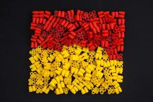 Plastic bricks of yellow and red on a black background photo