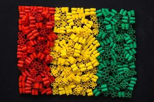 Plastic bricks of red, yellow and green on a black backgroun photo