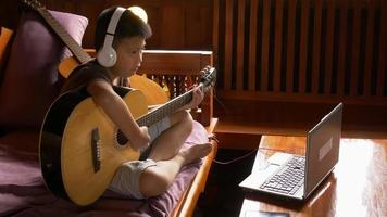 Boy learns to play guitar online  at home video