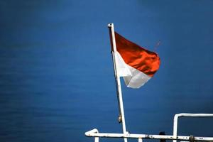 Indonesia National Flag waving at the blue sea photo