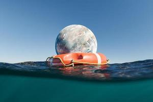 Planet with life buoy In ocean photo