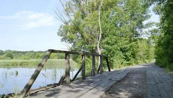 Viejo puente de madera permanente sobre el río en el fondo de color foto