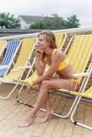 Beautiful young woman sitting on the sun lounger next to the pool photo