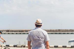 Man looking at the sea, standing at the sea port photo