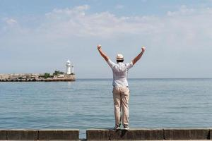 Man standing on the pier with sea and lighthouse on the background photo