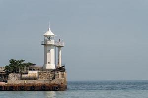 antiguo faro en la costa del mar foto