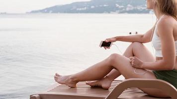 Woman sitting on the sun lounger listening to the music photo