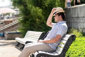 Young guy in the hat sitting on bench in the park or in the sea port photo