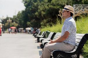 Man sitting on the bench on the sea embankment, having a rest photo
