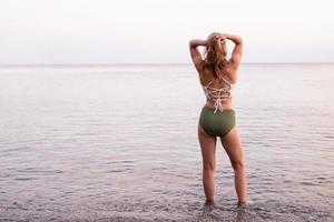 Young sportive woman standing on stony beach looking at the sea photo