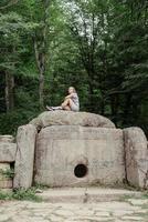 Mujer sentada sobre un gran dolmen de piedra en el bosque mirando a otro lado foto