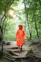 Mujer feliz en impermeable naranja caminando en el bosque foto