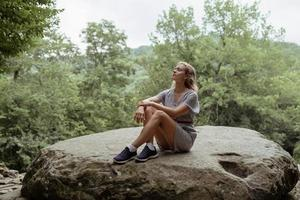 Woman sitting on a big rock in the forest, having rest or meditating photo