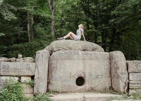 Mujer joven sentada sobre un gran dolmen de piedra en el bosque mirando a otro lado foto