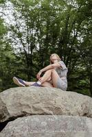 Mujer joven sentada sobre una piedra grande en el bosque mirando a otro lado foto