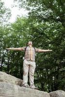 Joven parado sobre una gran roca en el bosque mirando a otro lado foto