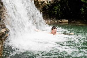 Hombre nadando en el río de la montaña con una cascada. foto
