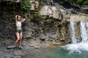 Young sexy woman in swimsuit enjoing the waterfall photo