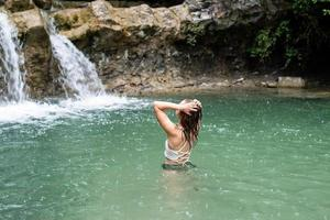 Woman swimming in the mountain river with a waterfall photo