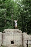 Young woman standing on a big rock in the forest looking away photo