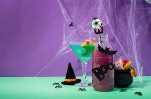 Scary colorful Halloween cocktails with party decorations on purple photo
