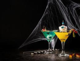 Scary colorful Halloween cocktails with party decorations on dark photo