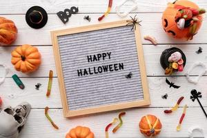 Happy Halloween words on gray letter board with candy flat lay photo