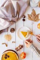 Tarta de calabaza casera con hojas de otoño sobre fondo rústico, vista superior foto