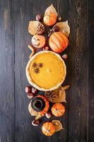 Homemade pumpkin pie with autumn leaves on rustic background, top view photo