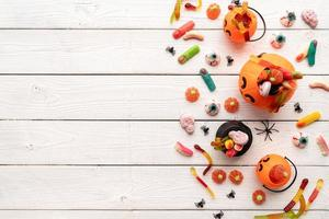 Colorful sweets for Halloween party on white wooden background photo